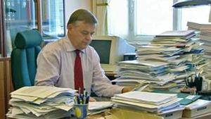 Raimo Sailas i sitt arbetsrum, med stora pappershögar på skrivbordet.