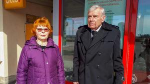 En dam och en man står framför en ingången till en servicestation.