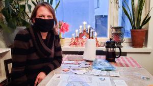 En kvinna i svart munskydd sitter vid ett köksbord. På bordet ligger ett brädspel föreställande Sibbo.