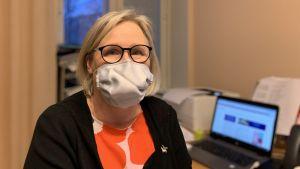 Kvinna i kontorsmiljö, bär munskydd.