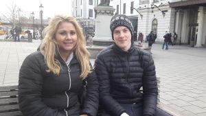 Samuel Karlsson och Hanna Granström på en bänk utanför centralstation, ler mot kameran.