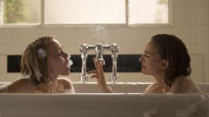 Kate (Lily-Rose Depp) och Laura (Natalie Portman) sitter i ett badkar och röker.