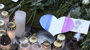 Ljus och ett pappershjärta på marken utanför Frankrikes ambassad i Helsingfors.