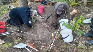 Två personer på huk vid en utgrävningsgrop.