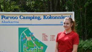 En kvinna i röd t-skjorta står framför skylt med karta över campingområdet.