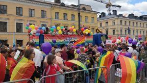 Människor på prideparad i Helsingfors. En lastbil i mitten.