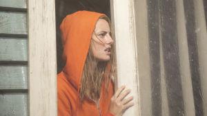 Haley gläntar på balkonsdörren och möts av regnet utanför.