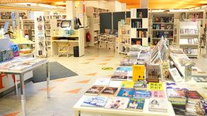 ett stort bord fullt med böcker. I bakgrunden mera böcker i bokhyllor.