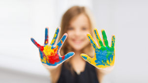 En flicka visar sina händer som är täckta av olika färgs målärger till kameran.