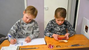 Två barn sitter vid en gammal träpulpet. Pojken till vänster ritar medan flickan till höger räknar på en miniräknare.