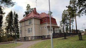 Villa Solhaga i Grankulla, bakom en lyktstolpe, fotografetar bakifrån. Huset har ett rött plåttak, med en grusväg som går runt huset och en grön gräsmatta.