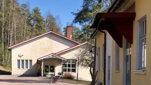 Ett beige skolhus med två cyklar parkerade framför. I förgrunden syns fasaden på en annan byggnad.