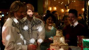 Tommy och Stisse stpr och tittar på en tårta på en fest.