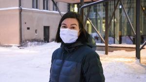 Kvinna i munskydd står på tom och snöig skolgård.