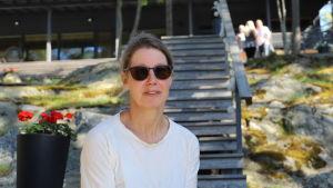 En kvinna i solglasögon sitter på en trappa vid en stuga utomhus.