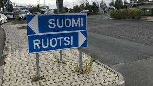 """Trafikskylt där en pil visar riktningen """"Suomi"""" och en annan visar riktningen """"Ruotsi""""."""