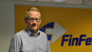 Mats Rosin står framför en gul vägg med företagets logotyp på.