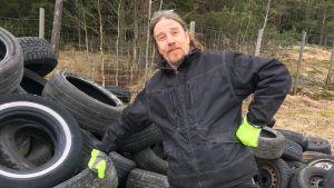 Jukka Vahtera och en hög med gamla bildäck.