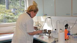 En kvinna i vit labbrock står och jobbar i ett laboratorium.