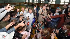 En läkare i vit rock i mitten, många journalister med mikrofoner omringar läkaren.