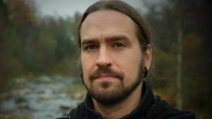 Mathias Lillmåns ser in i kameran, i bakgrunden skog och en fors. Svart jacka. Långt hår i svans. Piercing i näsan.