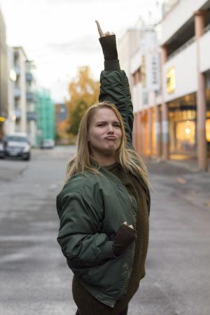 Sanna Helander poserar som Freddie mercury, med en arm lyft uppåt och fingret pekar mot himlen.