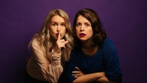 Blond kvinna håller fingret framför munnen, mörkhårig kvinna ser häpen ut