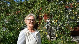 En medelålders kvinna står framför ett rött hus och ett päronträd.