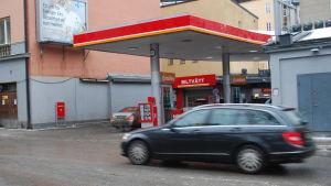 En bil kör förbi en bensinstation.