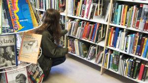 En kvinna sitter på huk vid en hylla med böcker på ett bibliotek.