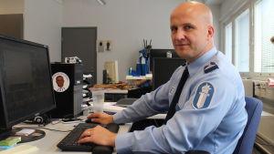 En man utan hår ser in i kameran. Han har på sig en ljusblå kragskjorta med polisens logo på armen, och sitter vid ett arbetsbord med händerna på tangentbordet. Framför sig har han en dator, och i bakgrunden finns ett tomt kontor.