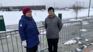 Två personer står framför ett stängsel, i bakgrunden Torneå-Haoaranda resecentrum