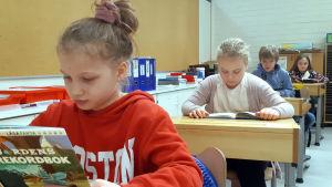 Skolelever läser i ett klassrum.