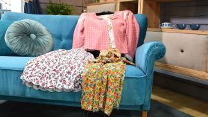 En blommig kjol, en rosa jacka och en blommig klänning som är sydda av återvunna tyger. Plaggen ligger framlagda på en blå sammetssoffa.