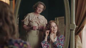 Spegelbild där kronprinsessan Märtha sitter vid ett sminkbord. Ragni står bakom med ett halsband i handen.