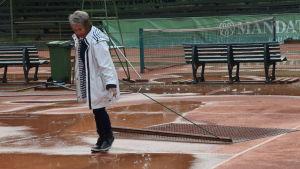 En kvinna drar en så kallad matta efter sig med vilken hon torkar upp en regnvåt tennisbana.
