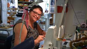 Riitta-Leena Norberg sitter vid sin symaskin och syr.