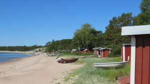 Hangö, Gunnarstrand en solig sommardag med knallblå himmel. Rödmålade fiskebodar och båtar längs sandstranden.
