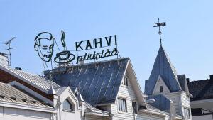 En skylt på ett tak i Hangö. Det står kahvi piristää på den gamla reklamskylten.