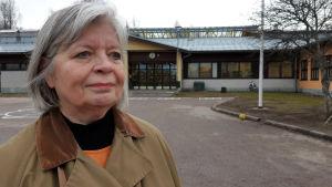 Arja Alho, en äldre kvinna med grått hår och brun rock står på en skolgård.