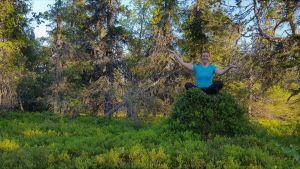 Joogaohjaaja istuu metsässä ja hymyilee