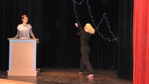 Flicka dansar på scen, kvinna står i en talarstol.