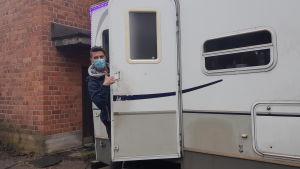 En man med munskydd tittar ut från en husvagn.
