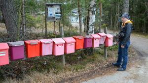 En man står bredvid en lång rad röda postlådor.