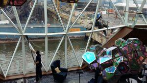En fönstertvättare tvättar fönster på utsidan av Mein Schiff 1. Fartyget är nybyggt och ligger ännu vid Åbovarvets kaj.