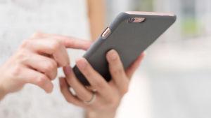 Kvinna petar på mobiltelefon
