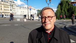 Patrick Chauvet, iklädd svart prästdräkt med röda detaljer poserar brevid en folktom gata