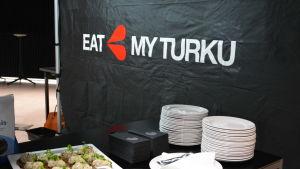 En svart vägg som det står Eat My Turku på, nedanför står tallrikar på ett bord.