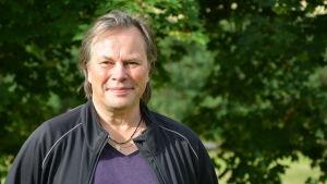 porträttbild av en man. Han står ute i grönskan och bär en svart jacka över en lila t-skjorta.