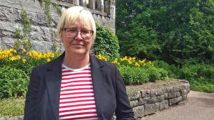 Pia Rosengård-Andersson med husfasad och natur i bakgrunden.